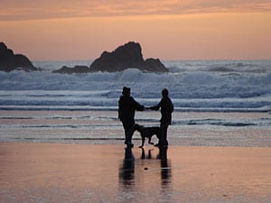 couple and labradoodle at the oregon coast beach